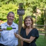 Pamela and John of painted horse winery holding a wine bottle in the vineyards