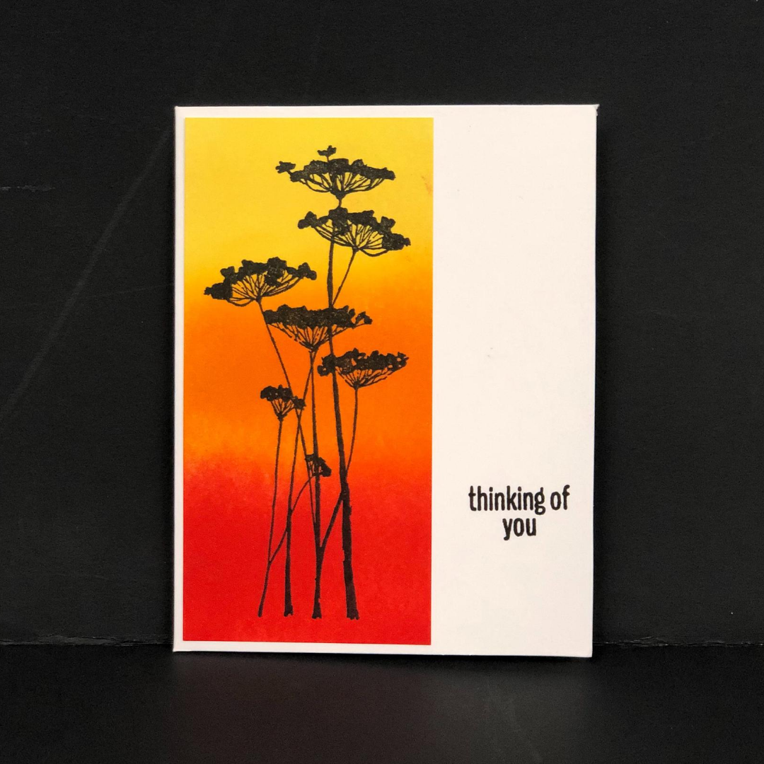 """Stamped card that says, """"thinking of you"""" with a yellow, orange, and red inked background."""