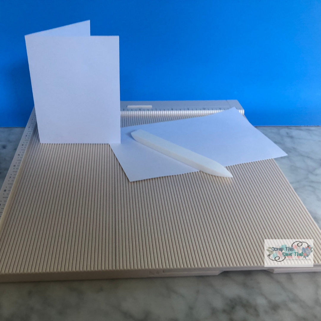 White greeting card blanks and a white bone folder sitting on top of a beige scoring board