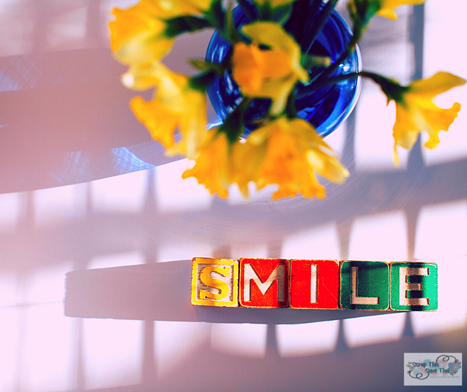 "Children's letter blocks spelling out the word, ""smile"" on a table with a blue vase filled with yellow daffodils."