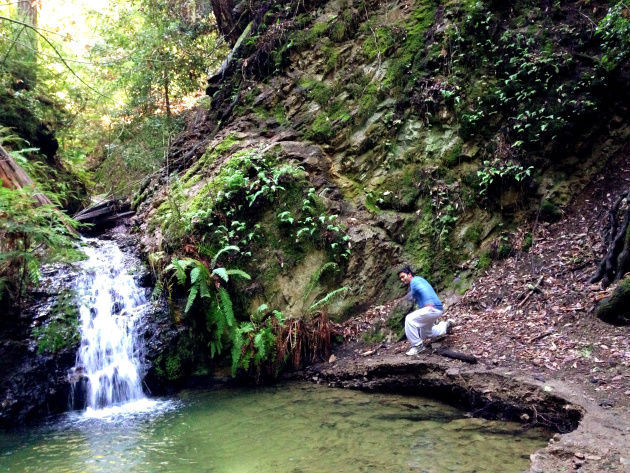Zubair Ahmed rock-slipping by a waterfall.
