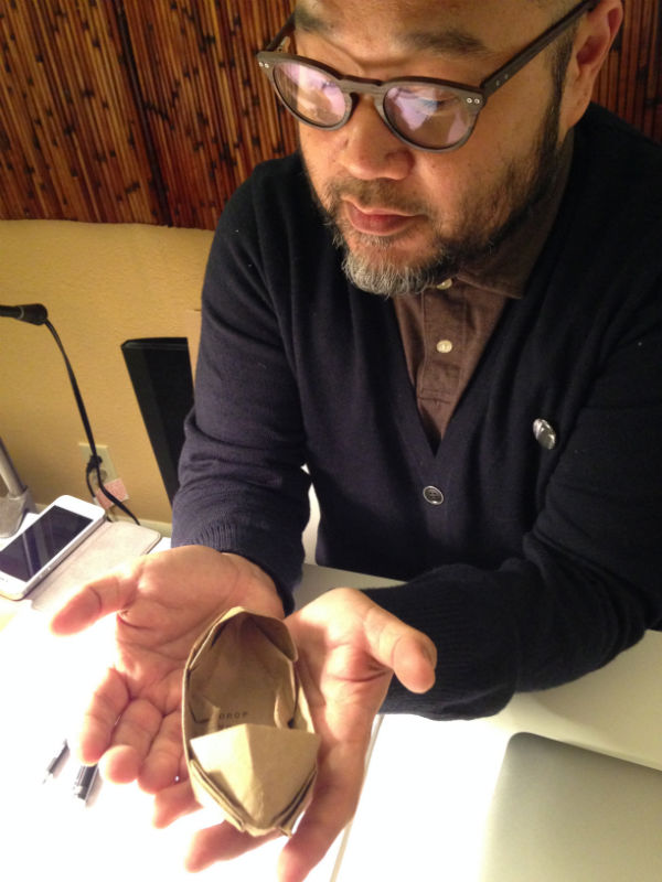 Poet Sam Roxas-Chua with one of his origami boats he hands out to audiences, Photo: Deanna Piowaty