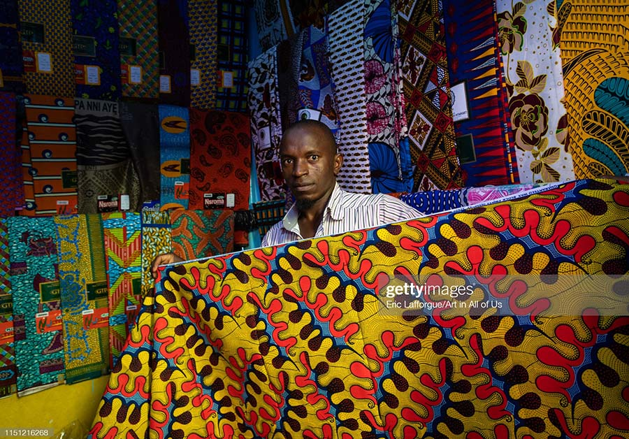 African seller with colorful african fabrics in a shop, Comoé, Abengourou, Ivory Coast.
