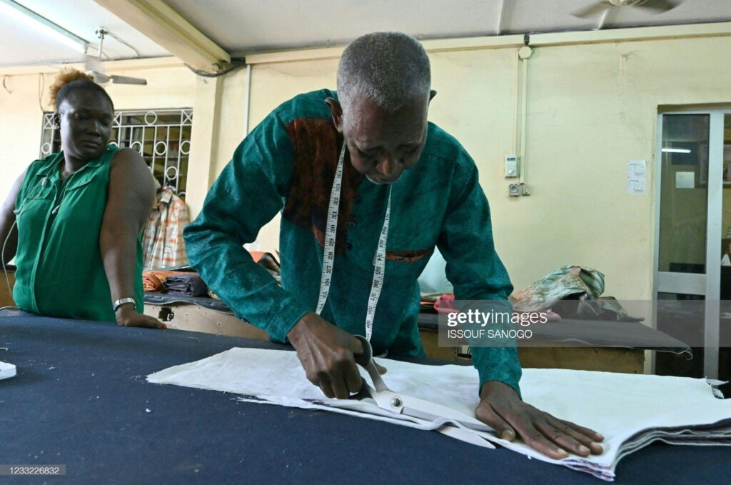 Ivorian-Burkinabe fashion designer Pathé Ouedraogo, known as Pathé'O, cuts fabric in his store in Abidjan on May 26, 2021.