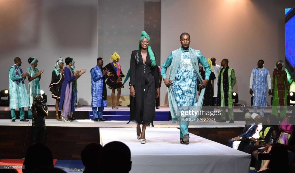 """Models present creations by Ivorian designer Pathe'O, who is known for being the creator of the shirts of late South African President Nelson Mandela, during the 10th """"Afrik"""" fashion show in Abidjan on June 14, 2015."""