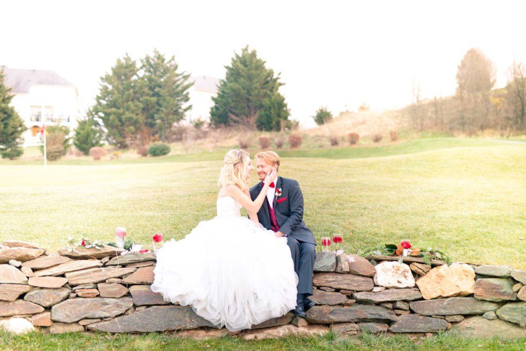 winter wedding couple sit on stone wall