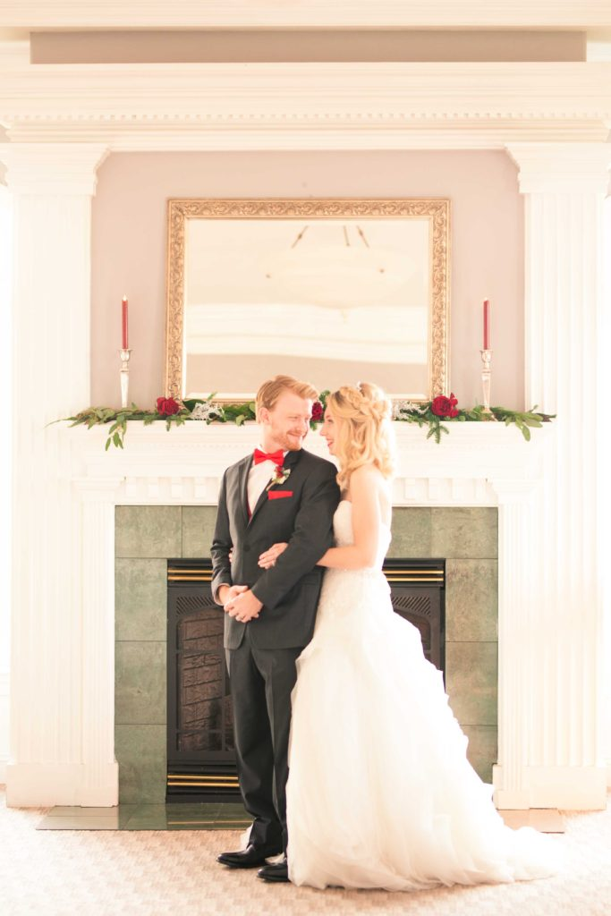winter wedding couple in front of fireplace