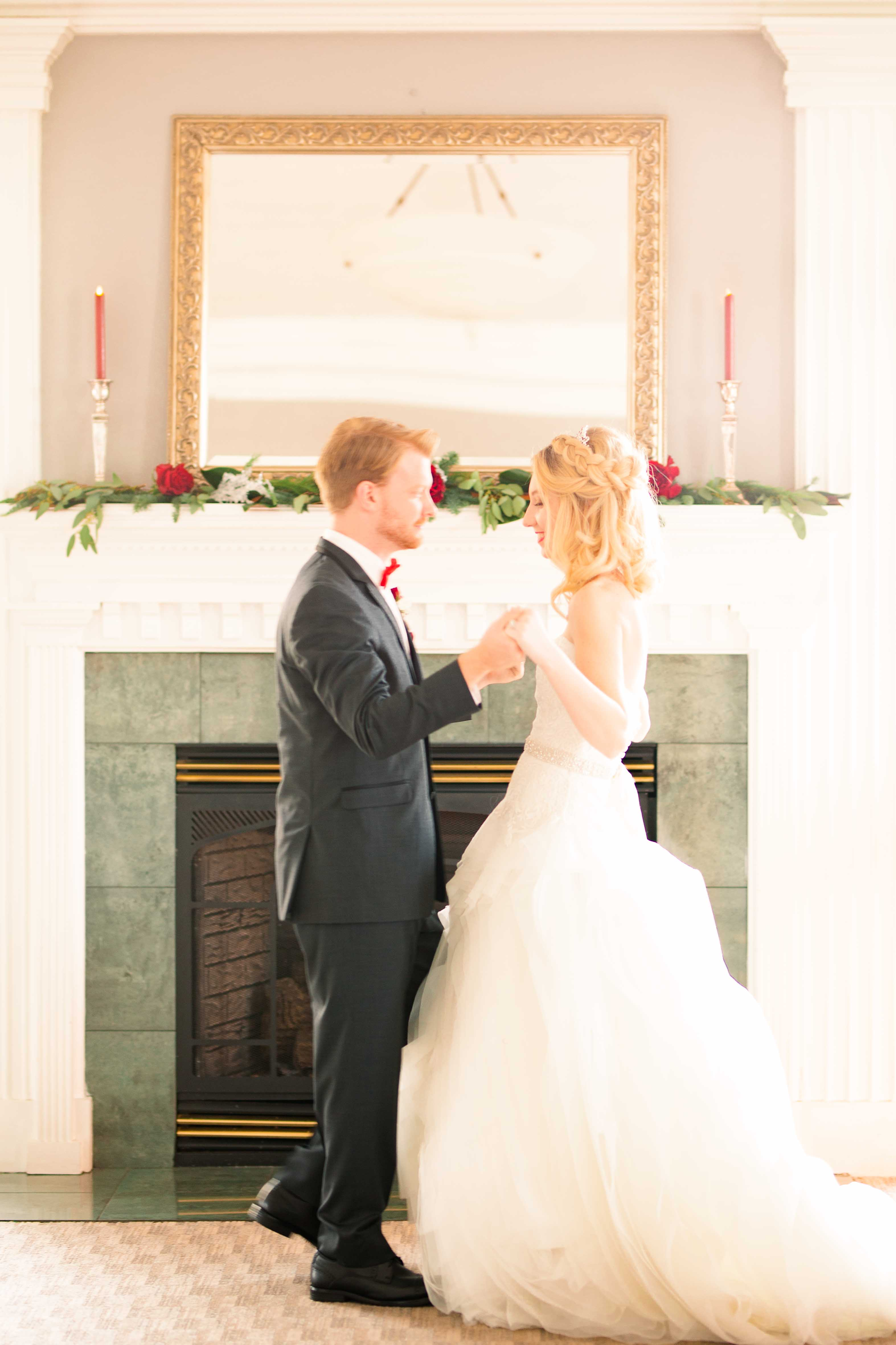 winter wedding couple dance in front of fireplace