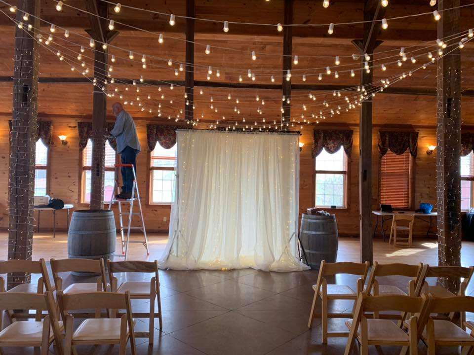 String lighting being hung above a dance floor for a wedding setup