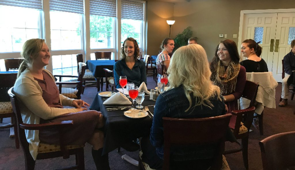 Students conversing during etiquette dinner
