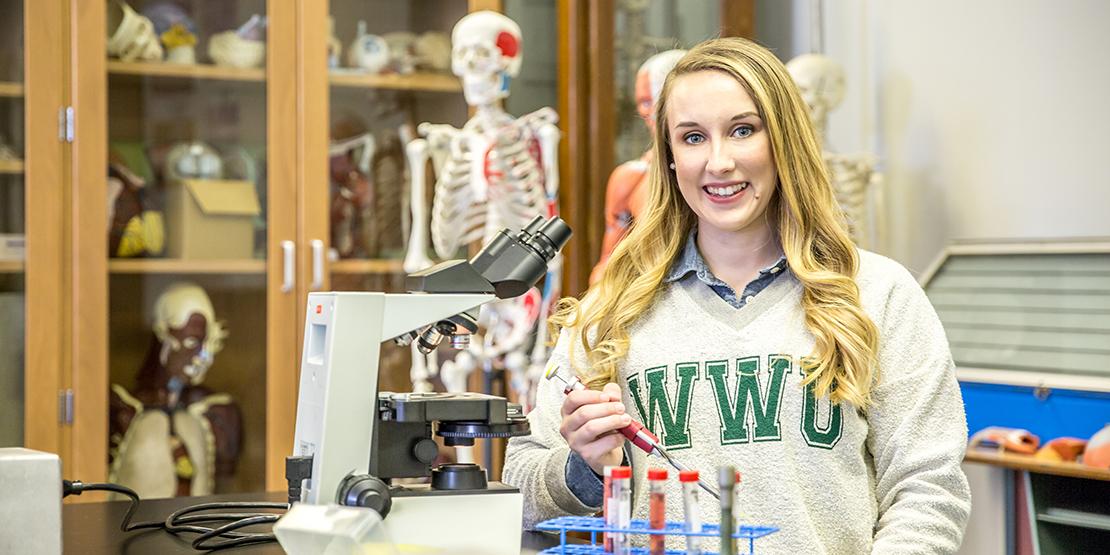 Ari Arnold posing with biology lab equipment