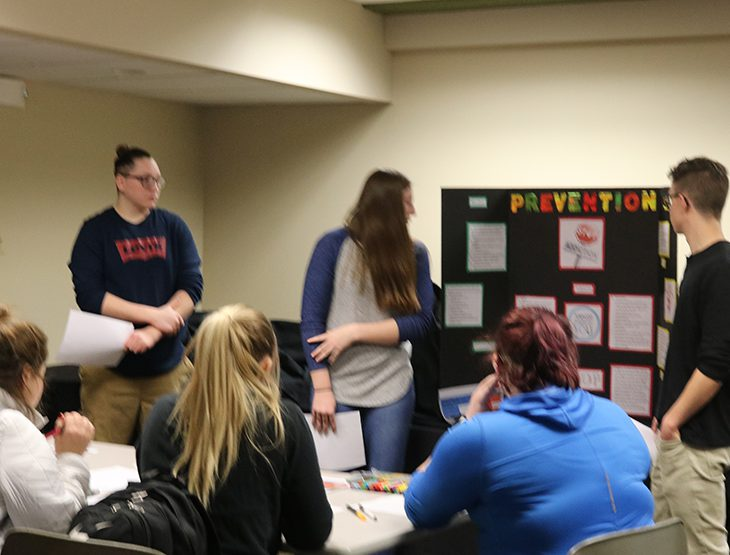 Students gathered around a poster board presentation