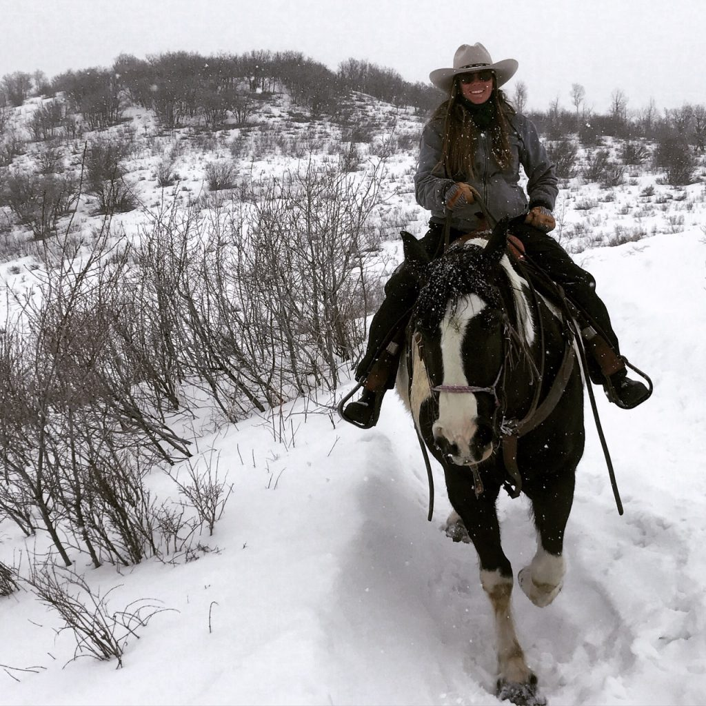 Mandy Griffey riding western on a horse in Colorado