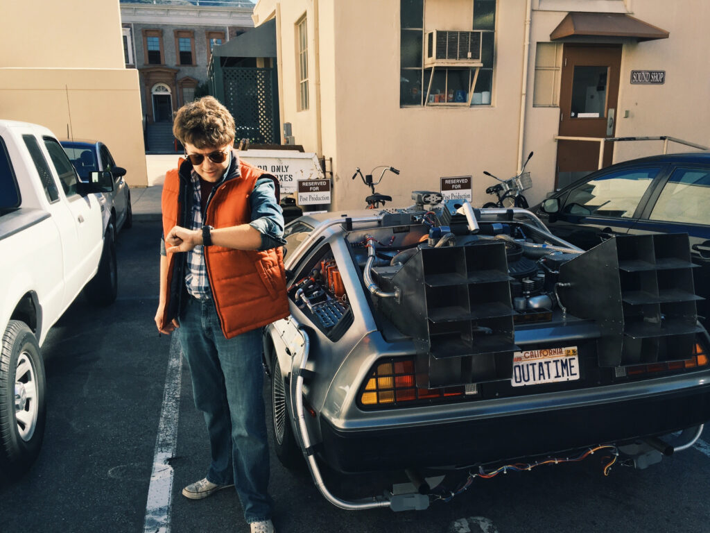 Joshua Potter posing as Marty McFly with the DeLorean from the Back to the Future trilogy.