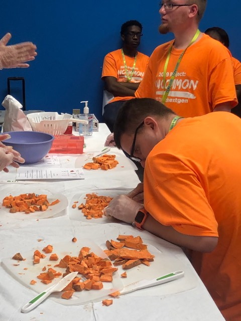 A young man in an orange shirt is carefully cutting sweet potatoes