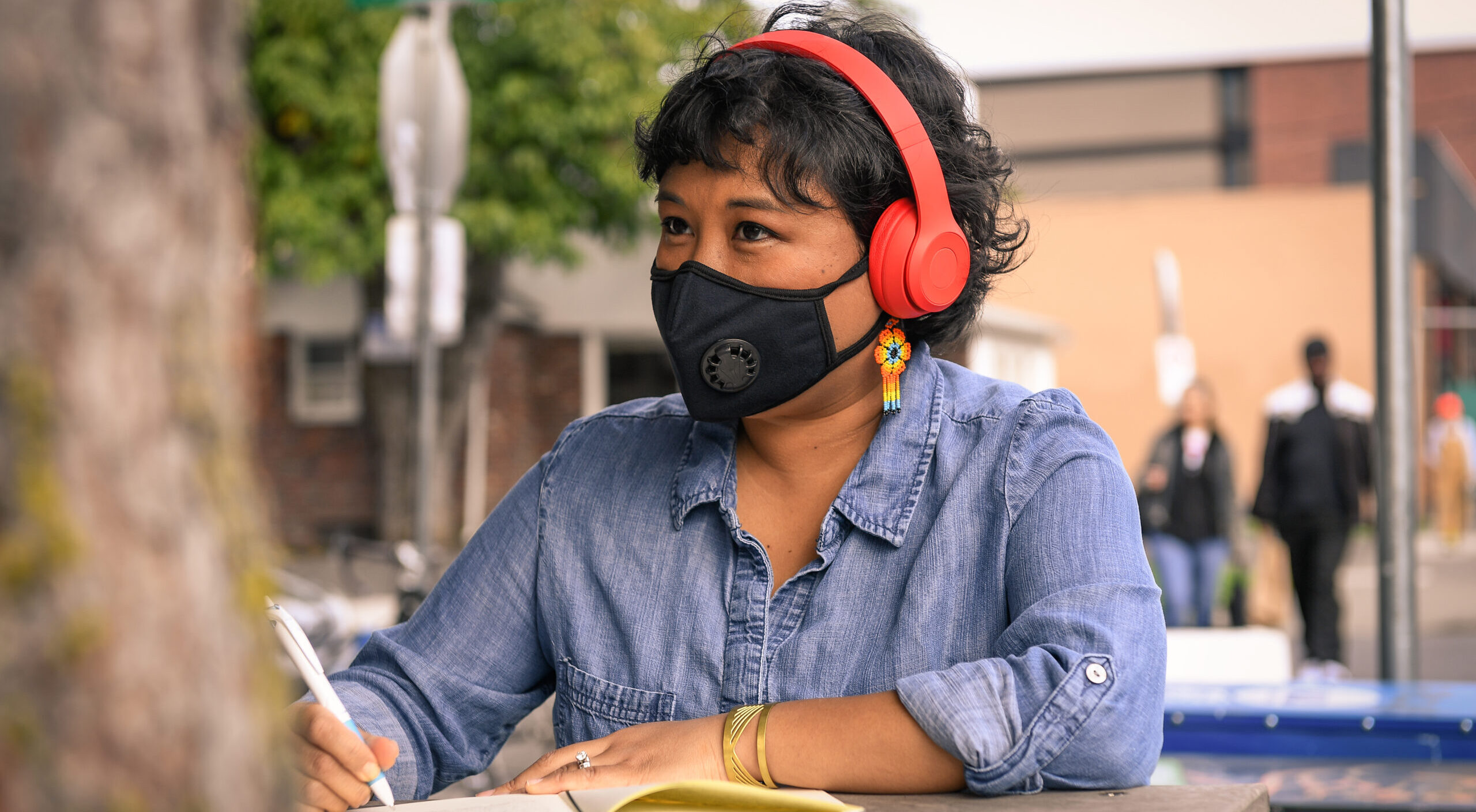 Close-up of a Filipinx woman with a filtering face mask, sitting at a table with notebook and pen. She has colorful flower earrings and headphones on while looking into the distance.