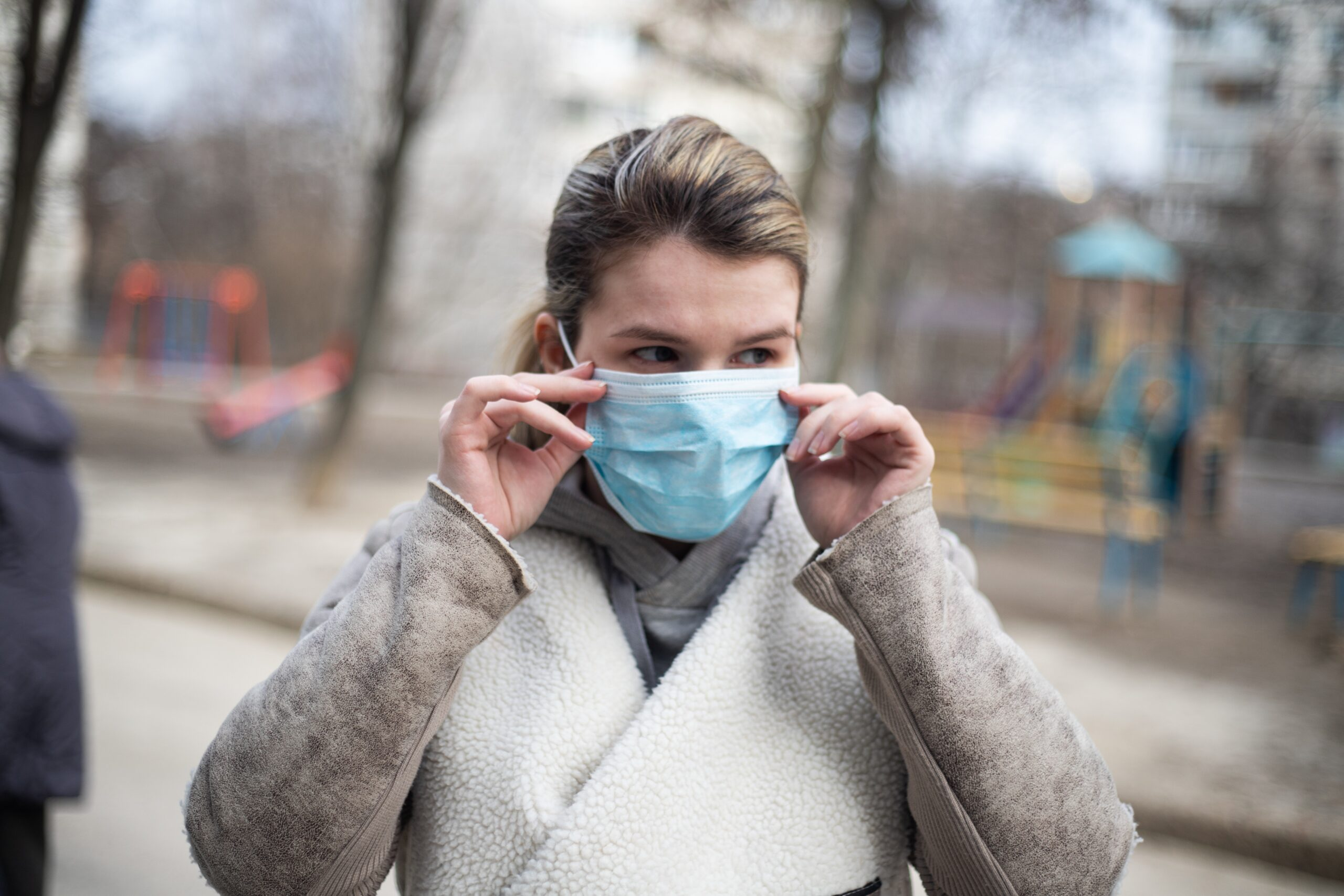 A young woman is fixing a surgical mask on her face while outsite