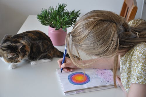 Image of a woman writing and drawing in a journal while a cat watches her