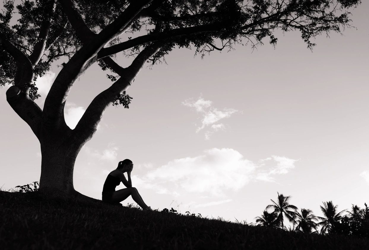 A black and white image of a person holding their head in their hands under a tree