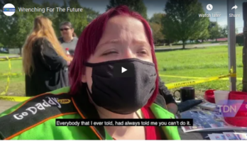 Image still from the video of a woman wearing a black mask