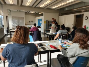 People are seated at tables in a classroom art studio. They have canvas and paints and are painting while the instructor talks to them.