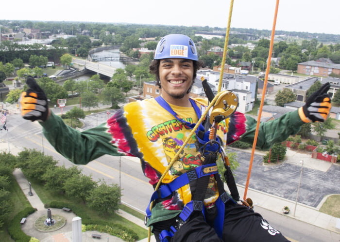 A smiling young man wear a tie die shirt and a helmet as he is suspended in a harness above the city