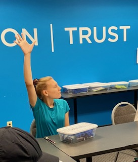 A teen raises her hand while in a classroom. She has a bin of materials on the table in front of her.