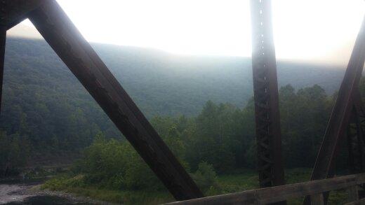 Sun coming up over the mountain as I cross a trestle bridge.