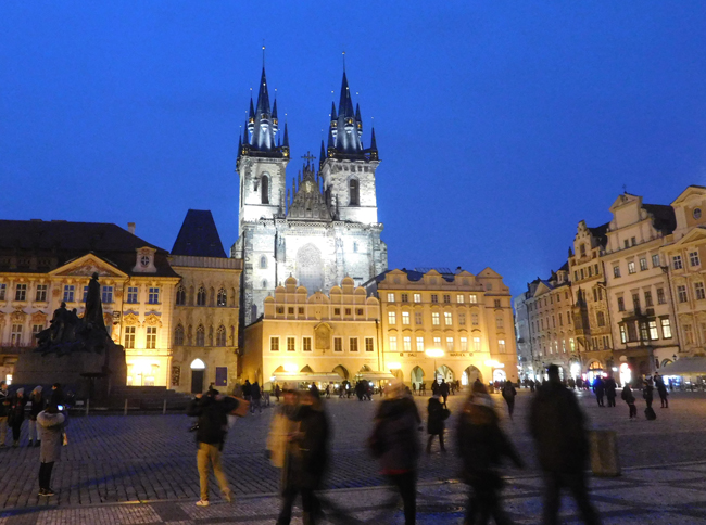Old Town Square with Jan Hus silhouetted on the left and The Church of Mother of God before Týn brightly looking down on us.