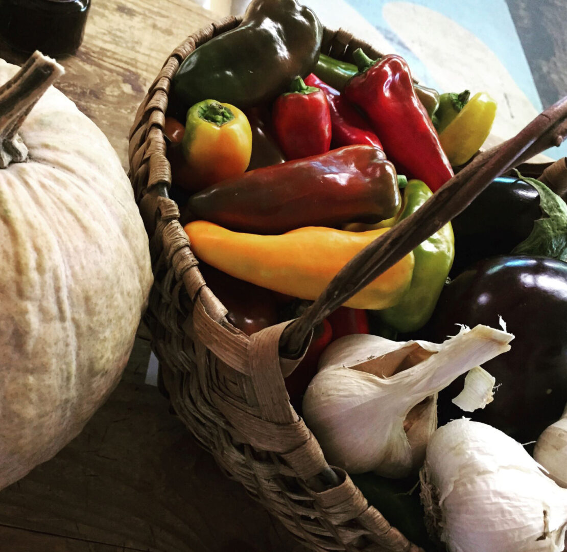 a basket of bell peppers and garlic
