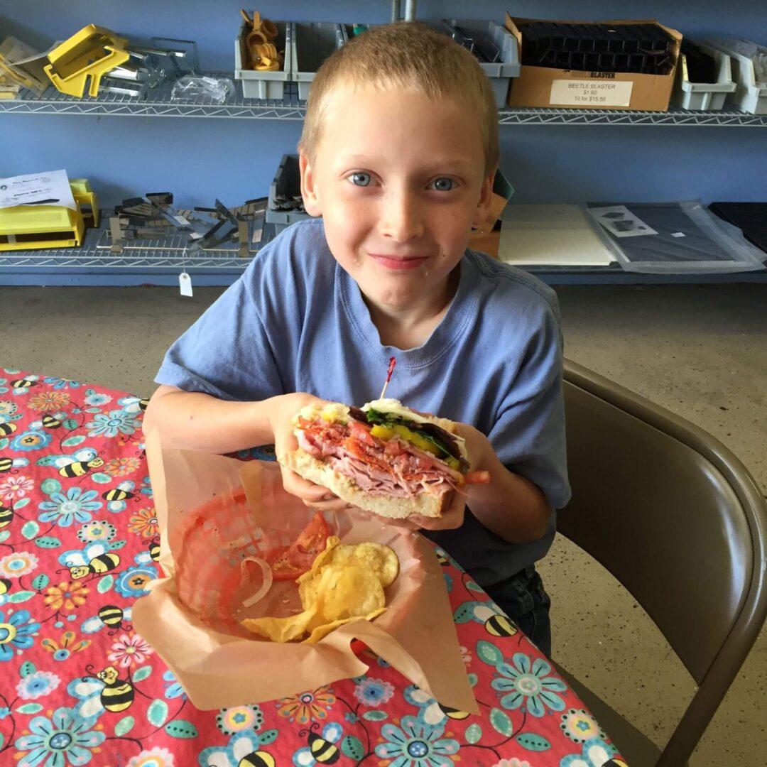 a blonde boy holding a sandwich