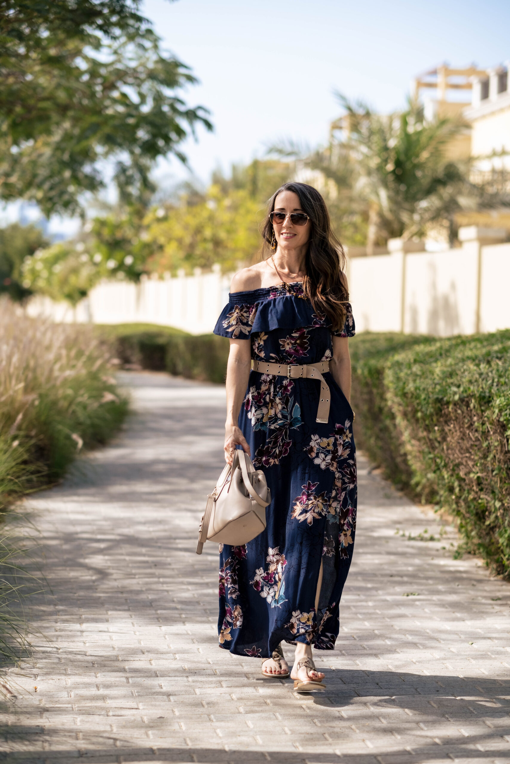 Walking to camera with floral off the shoulder dress, neutral belt, bag and rose gold sunglasses