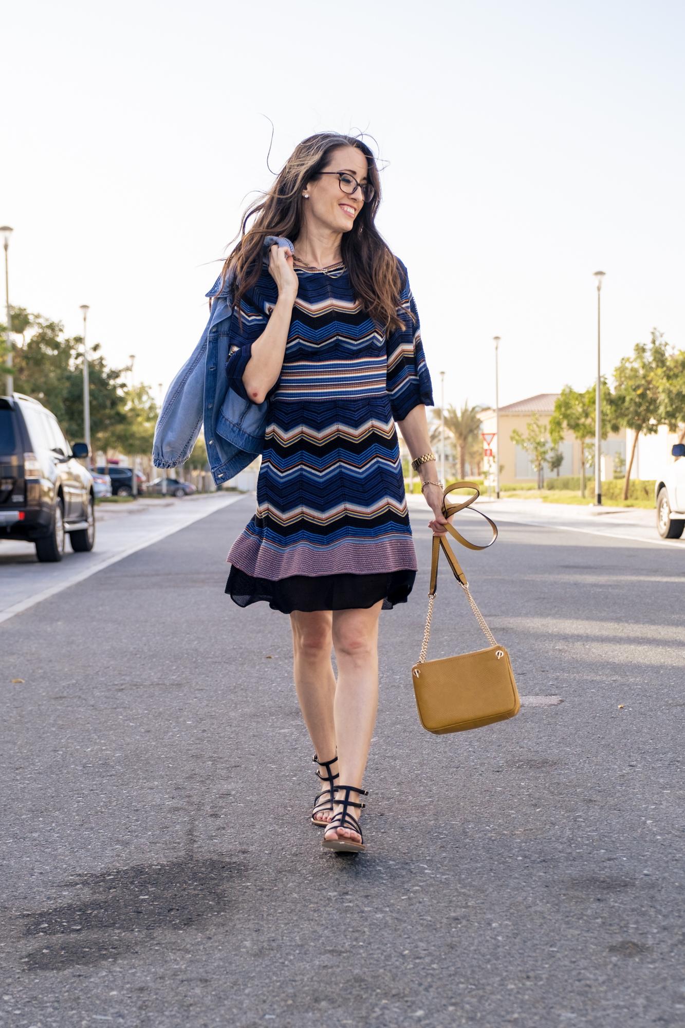walking on the street towards the camera in a zig zag print dress