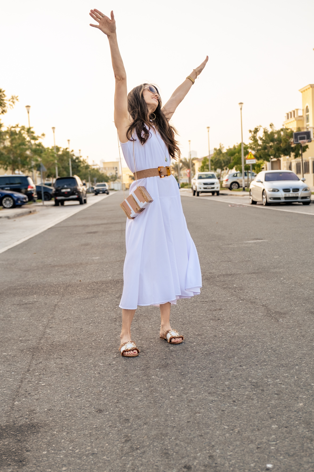 Standing in the street, hands up, face to the sky smiling