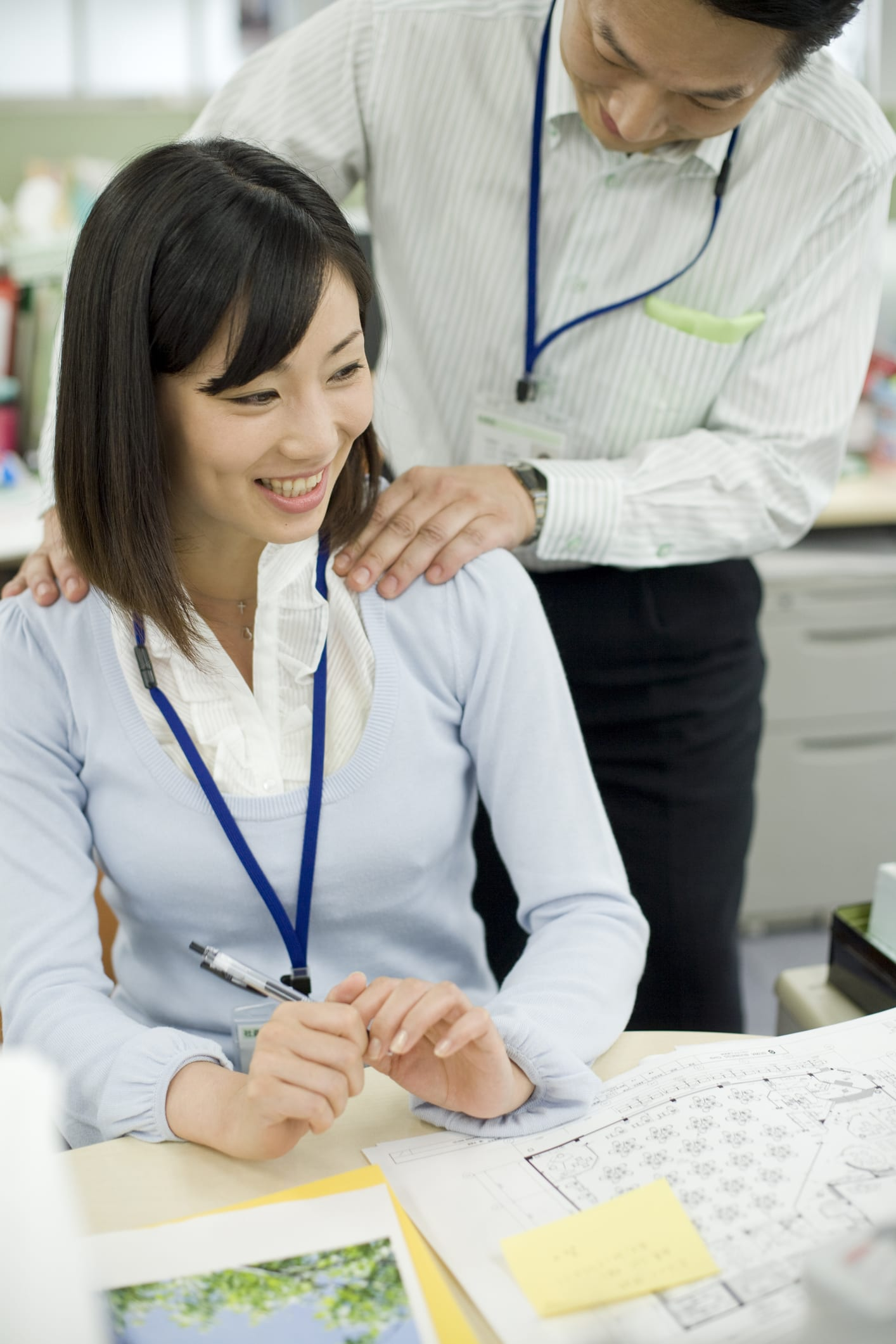 Male boss giving female office worker shoulder massage