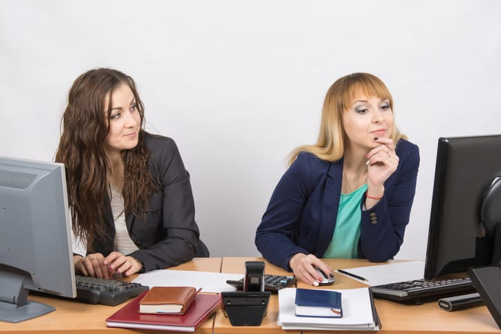 Office worker looking with distaste at the colleague sitting next