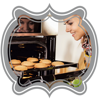 A woman smiling and removing a hot baking pan with cookies on it from her oven.