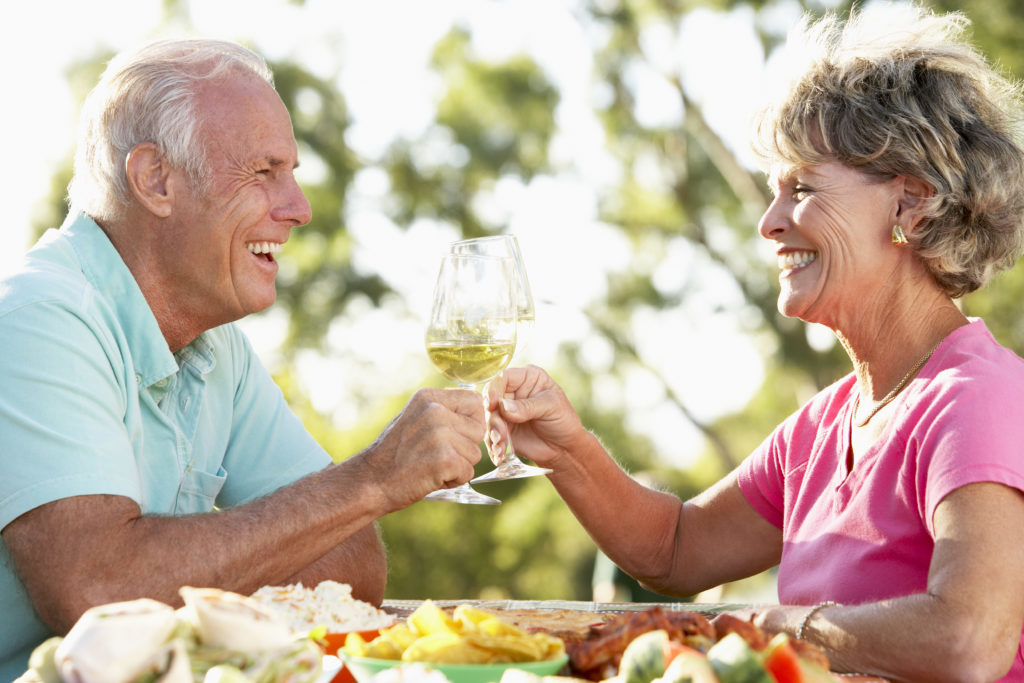Elderly couple toasting that they have no worried because they have the best fit with the dentures they got from Dr. Hickey at Sound to Mountain Dental in Tacoma, WA.
