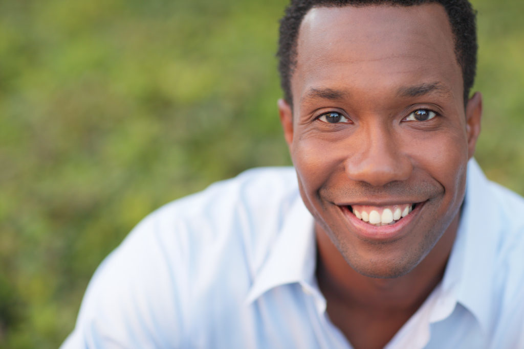 Man looking at the camera and smiling without being able to tell has a dental bridge to correct his smile.