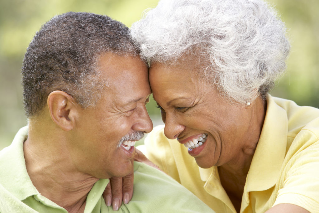 Older black couple smiling because they know they have perfectly fitted dentures from Sound to Mountain Dental in Tacoma, WA.