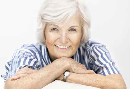 Older lady showing off her dental crown which you can't tell from her natural teeth.