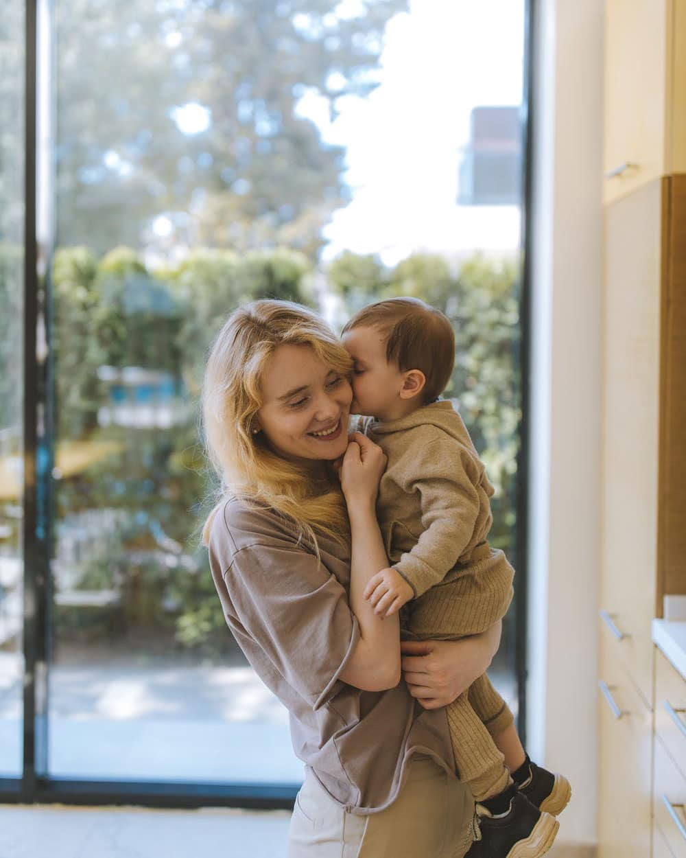 Mother and child in front of a large sliding patio door in home
