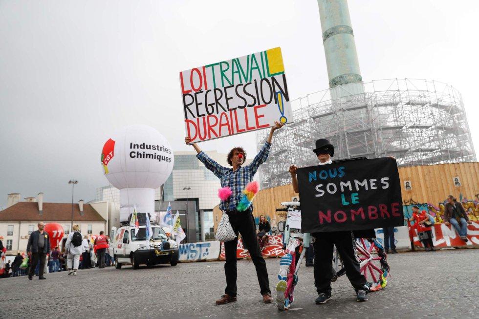 """Un manifestante francés alza una pancarta donde se lee: """"derecho laboral - dura regresión"""" al lado de la pancarta de otro manifestante que dice: """"Somos números"""", como parte de la protesta contra la reforma laboral, en París."""