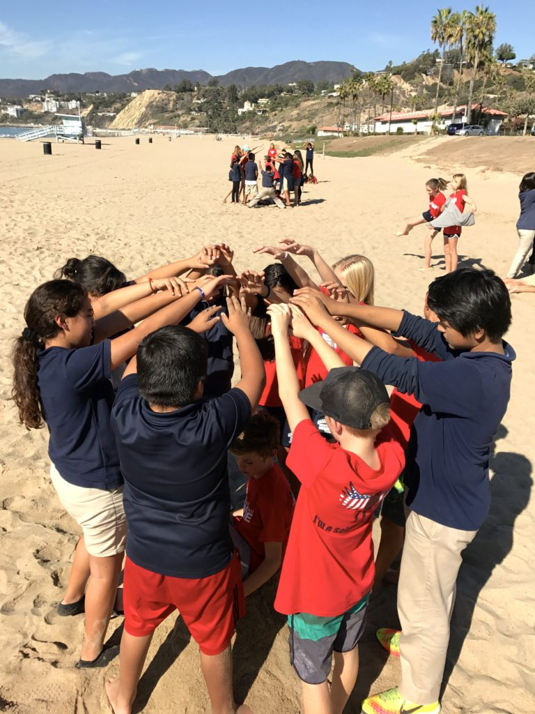 Students participate in team building activities at the beach cleanup.