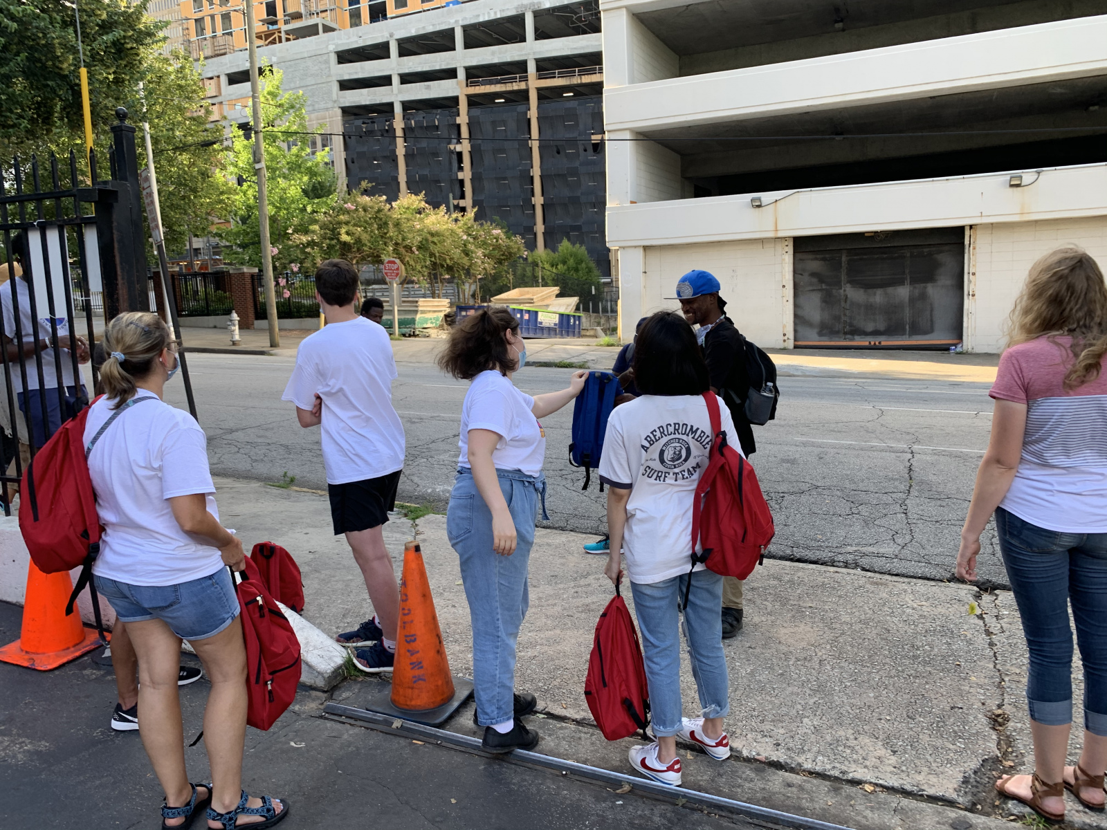 Passing out backpacks in front of SafeHouse Outreach