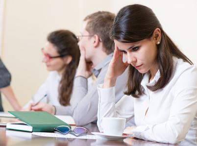 Tired business woman with headache at seminar