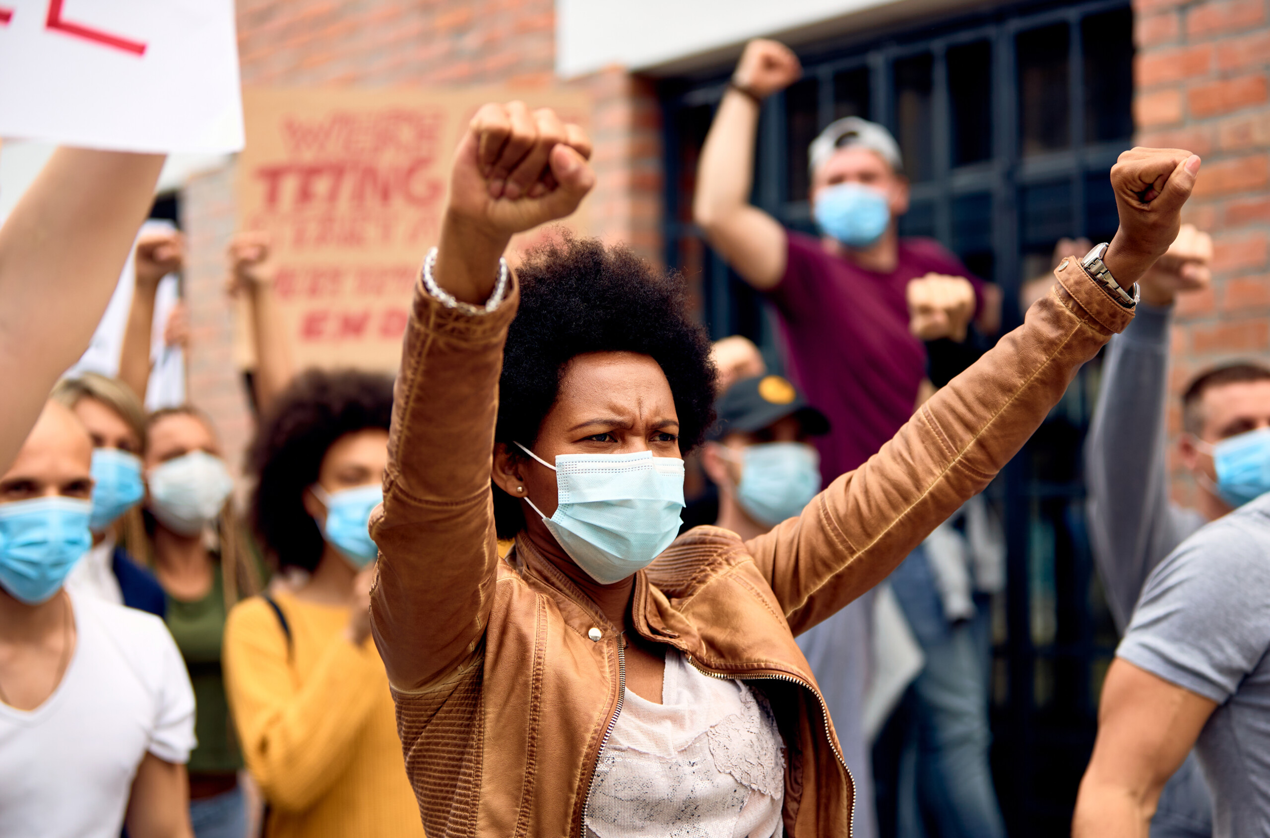 Black woman with raised fists wearing protective face mask while supporting anti-racism demonstrations.