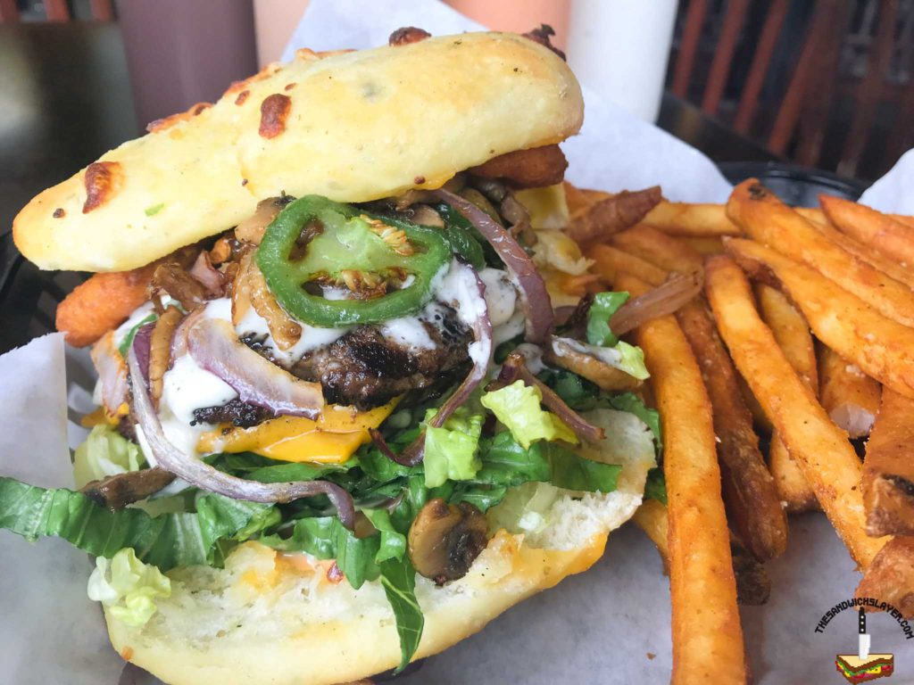 Rockfire grill's OMG burger with onion rings, cheddar cheese, mushroom, garlic aioli and lettuce on house baked flatbread
