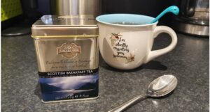 A tin of Scottish Breakfast tea sits on a counter beside a mug with a Loch Ness monster tea strainer poking out