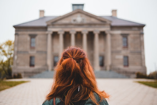 A woman with wavy auburn hair stands in front of a brown stone building